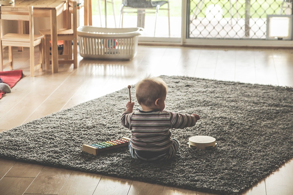 Image: kid playing on a rug in a vacation apartment